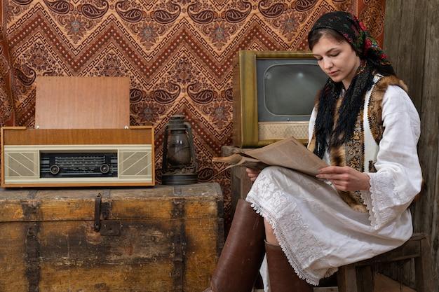 Frau in alten nationalen kleidern sitzt auf dem stuhl zwischen vintage-raum und liest zeitung, retro-tv, radio und gaslampe auf der holzkiste