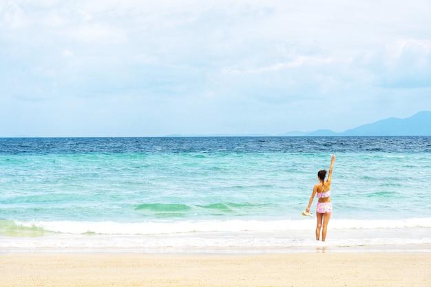 Frau in anhebender hand des bikinis und in schauender ansicht des tropischen strandes