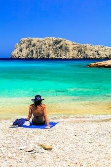 Frau in badeanzug, die auf dem schönen strand kounoupa in astypalea insel, griechenland badet