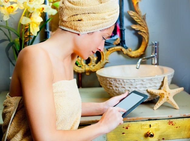 Frau in bathroomreading ebook tablette