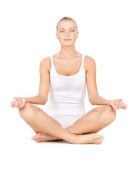 Frau in baumwollunterwäsche, die yoga-lotus-pose praktiziert