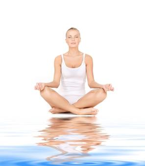 Frau in baumwollunterwäsche praktiziert yoga lotus-pose auf weißem sand
