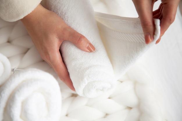 Frau in beige warmem gewand faltet die sauberen weißen handtücher und legt sie in einen metallgitterkorb auf schwarzem hintergrund. kopieren sie platz auf schwarzem hintergrund. sauberkeits- und organisationskonzept.