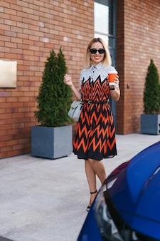 Frau in bewegung, die einen kaffee zu gehen hat, während sie in der nähe eines autos in der stadt geht
