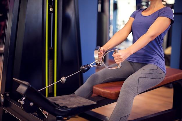 Frau in blauem hemd und kurzen haaren trainiert zurück im fitnessstudio. menschen-, fitness- und gesundheitskonzept