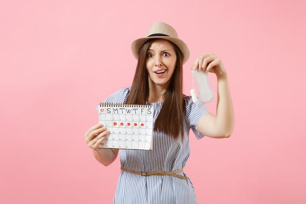 Frau in blauem kleid, hut mit damenbinde, tampon-kalender für weibliche perioden, überprüfung der menstruationstage einzeln auf rosafarbenem hintergrund. medizin, gesundheitswesen, gynäkologisches wahlkonzept. platz kopieren.