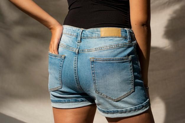 Frau in blauen denim-shorts mit in die tasche gesteckter hand, rückansicht