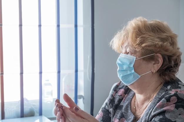 Frau in blauer medizinischer schutzmaske bleiben zu hause und schauen zum fenster. quarantäne