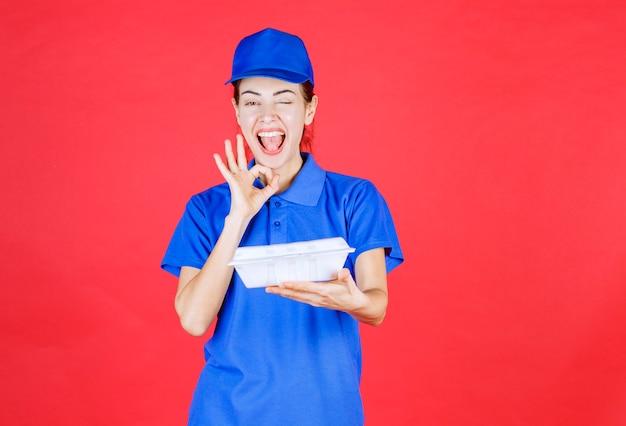 Frau in blauer uniform, die eine weiße plastikbox zum mitnehmen hält und ein zufriedenheitszeichen zeigt.
