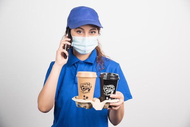 Frau in blauer uniform mit medizinischer maske, die am telefon spricht und zwei tassen kaffee auf weiß hält