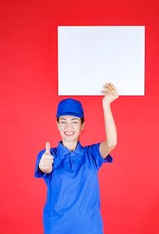 Frau in blauer uniform und baskenmütze, die einen weißen quadratischen infoschalter hält und erfolgreiches handzeichen zeigt.