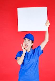 Frau in blauer uniform und baskenmütze mit einem weißen quadratischen info-schreibtisch und sieht überrascht und nachdenklich aus.