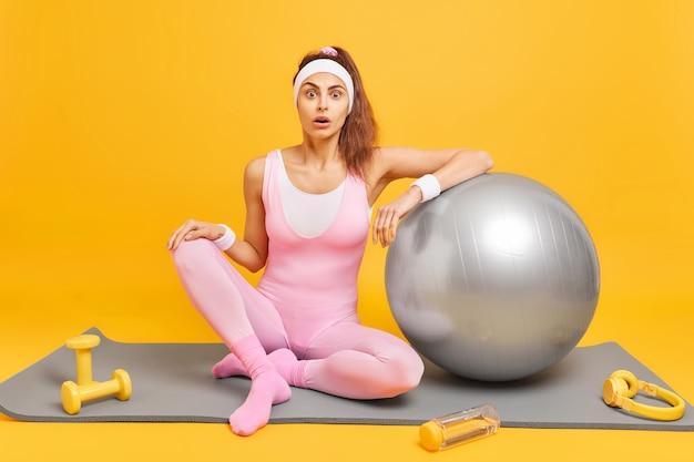 Frau in bodysuit-zügen mit fitnessball sitzt auf karemat, umgeben von hantelkopfhörern und einer flasche wasser isoliert auf gelb