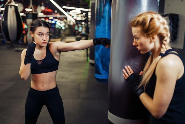 Frau in boxbandagen schlägt einen boxsack, boxtraining mit trainer. weibliche boxer im fitnessstudio, kickbox-training im sportclub, schlagübungen