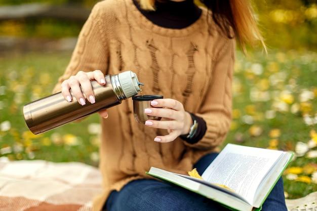 Frau in braun gestricktem sweather gießt heißen kaffee von der thermosflasche zur schale. interessantes buch im ruhigen herbstpark lesen. herbststimmung