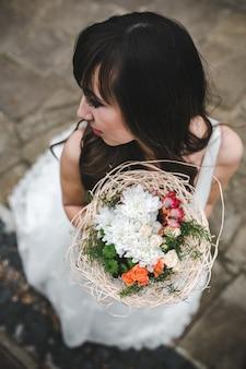 Frau in brautkleid posiert mit bouquet