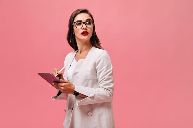 Frau in brille macht notizen in tablette. schöne brünette mit großen roten lippen im hellen anzug, der auf lokalisiertem hintergrund aufwirft.