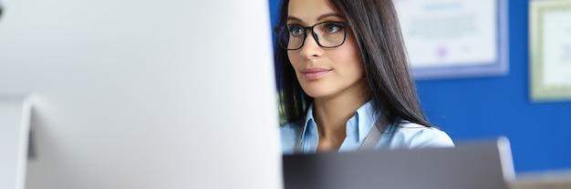 Frau in brille und blauem hemd sitzen am arbeitsplatz und schauen auf computerbildschirm.