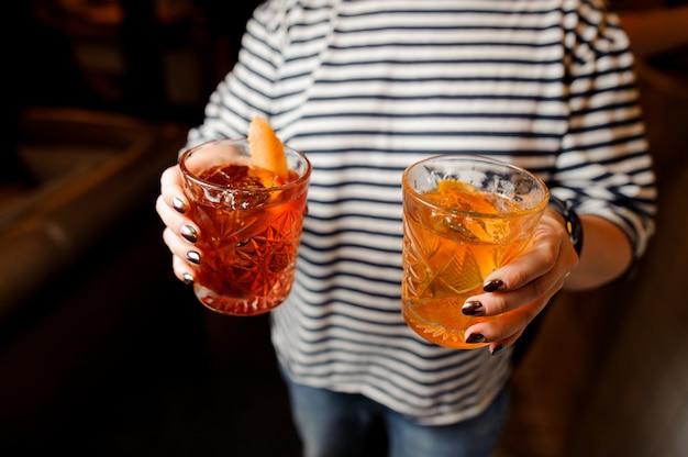 Frau in dem gestreiften hemd, das gläser mit frischen cocktails hält