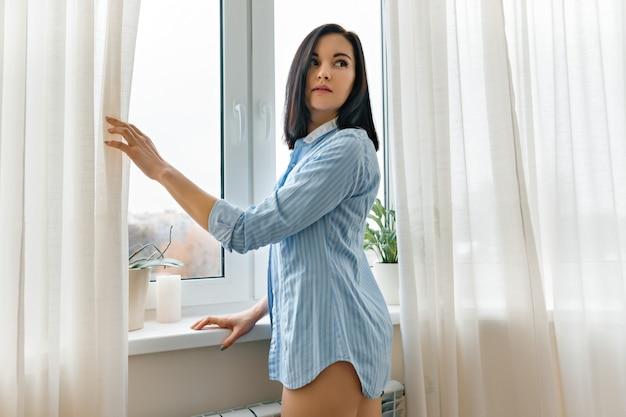 Frau in den blauen hemdöffnungsvorhängen