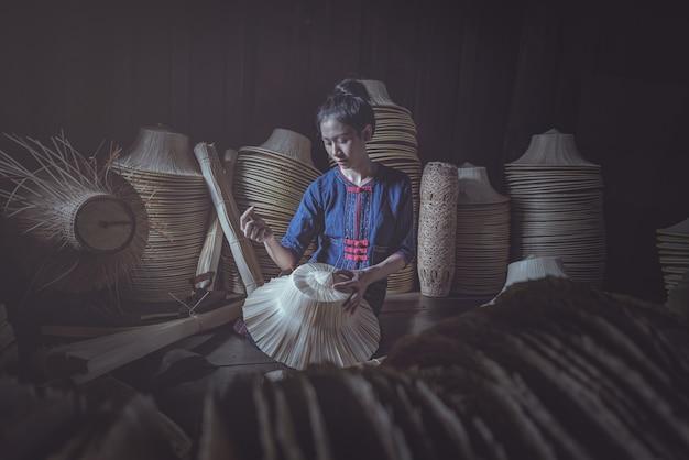 Frau in den ethnischen traditionellen nationalen thailändischen kostüm-spinnenden volkshüten.