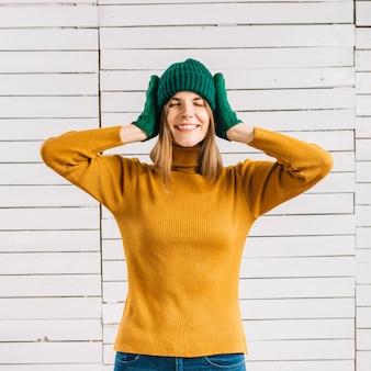 Frau in den gelben strickjackebedeckungsohren