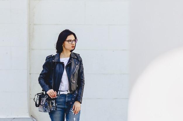 Frau in den gläsern in der lederjacke auf straße