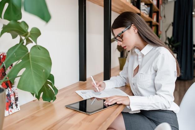 Frau in den gläsern informationen von der tablette in das büro schreibend