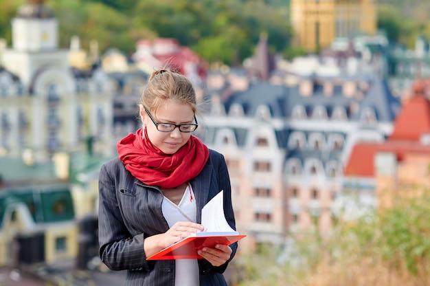 Frau in den gläsern mit dem roten buch auf stadthintergrund