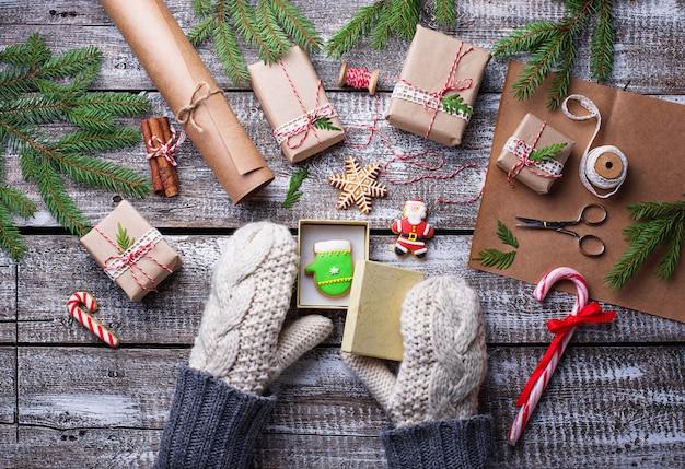 Frau in den handschuhen, die weihnachtsgeschenkkästen verpacken