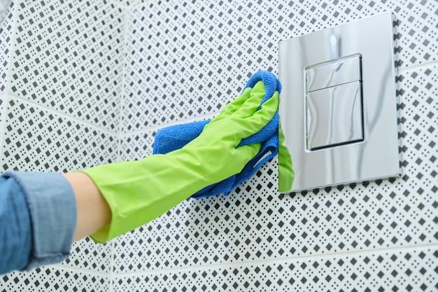 Frau in den handschuhen mit lappen, die reinigung im badezimmer, reinigung und polieren des chrom-toilettenknopfes auf gekachelter wand tun