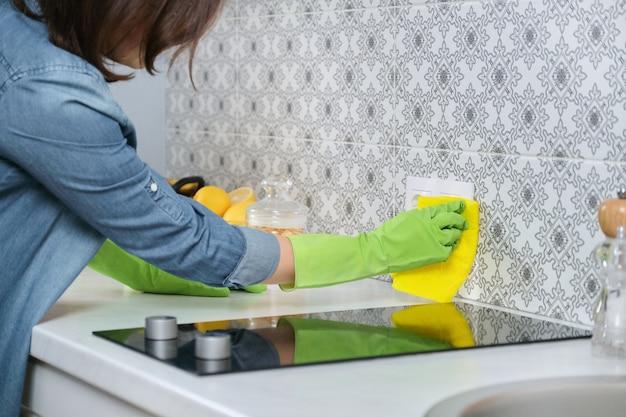 Frau in den handschuhen mit lappenreinigungshaus in der küche. weibliche waschreinigung, die geflieste wand poliert