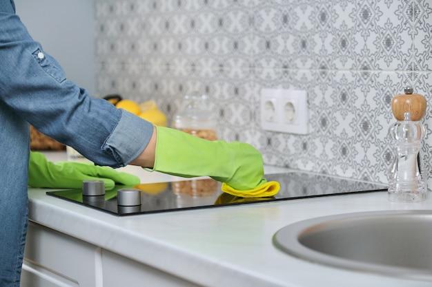 Frau in den handschuhen mit lappenreinigungsküche, waschendes elektrisches kochfeld auf arbeitsplatte von küchenmöbeln
