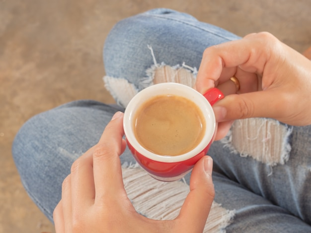 Frau in den heftigen jeans, die an der kaffeestube sitzen