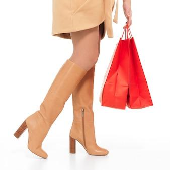 Frau in den herbststiefeln mit einkaufstaschen, die lokal auf weiß stehen