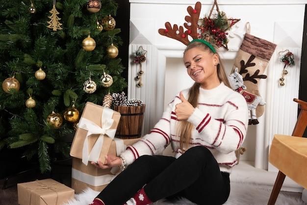 Frau in den hirschohren, die geschenk zeigen und daumen aufgeben.
