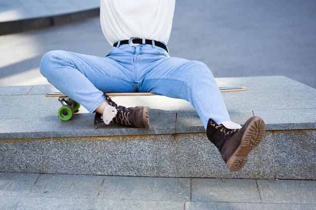 Frau in den jeans, die auf longboard sitzen