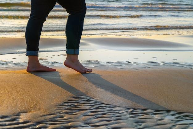 Frau in den jeans, die auf sandstrand bei sonnenuntergang gehen.