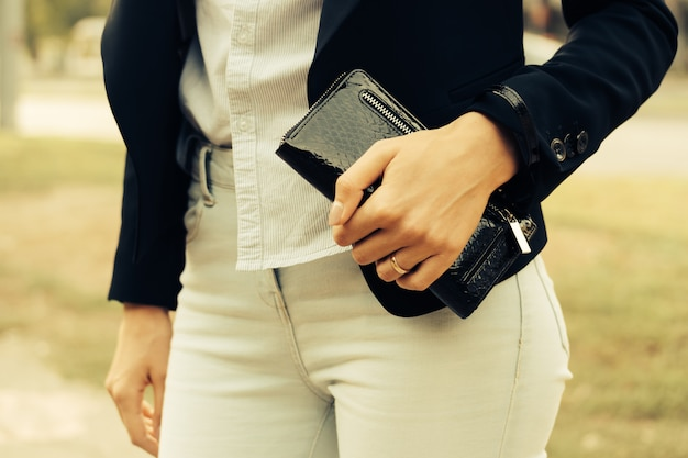 Frau in den jeans, im hemd und in einer schwarzen jacke, die draußen einen geldbeutel in ihrer hand hält