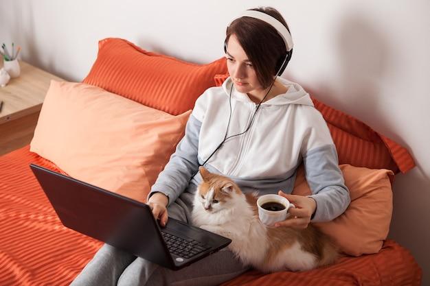 Frau in den kopfhörern, die auf dem bett mit einer katze sitzen. online-bildung zu hause und arbeit unter komfortablen bedingungen.