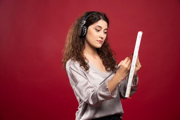 Frau in den kopfhörern, die auf leinwand malen.