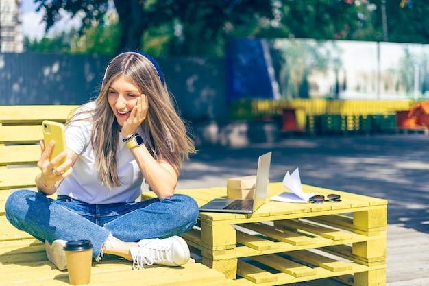 Frau in den kopfhörern, die einen videoanruf mit smartphone haben. glückliches und lächelndes mädchen, das draußen arbeitet und kaffee trinkt.