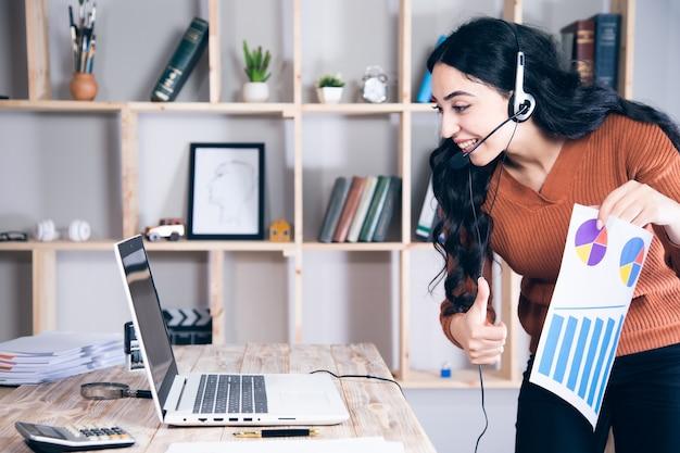 Frau in den kopfhörern, die im computerhandgraph sprechen