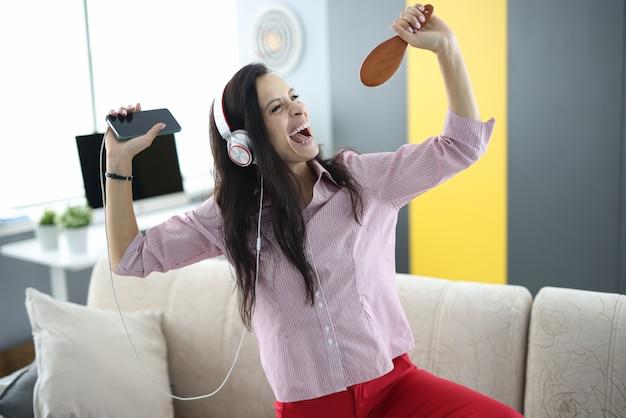 Frau in den kopfhörern, die zu einem pinsel singen