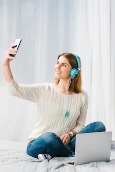 Frau in den Kopfhörern, die selfie nehmen