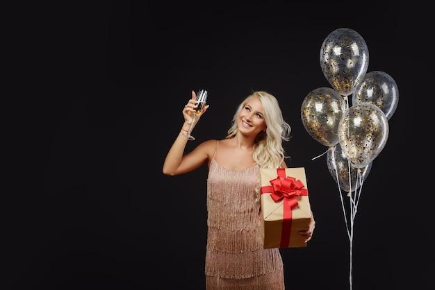 Frau in den luxuskleidern, die geburtstag oder weihnachtsfeier feiern. goldene luftballons und champagner