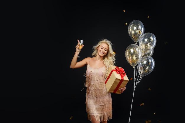 Frau in den luxuskleidern, die geburtstag oder weihnachtsfeier mit konfetti auf schwarz feiern