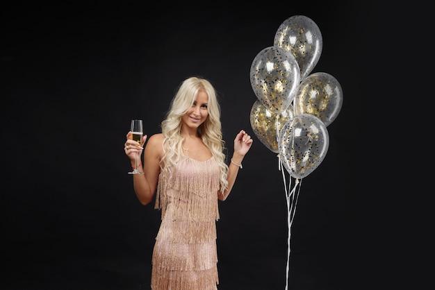 Frau in den luxuskleidern, die party feiern. goldene luftballons und champagner