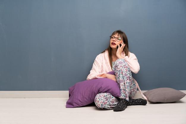 Frau in den pyjamas auf dem boden, der ein gespräch mit dem handy hält