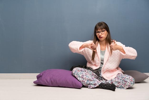 Frau in den pyjamas auf dem boden, der gut-schlechtes zeichen macht. unentschieden zwischen ja oder nicht